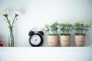 Weinlesewecker auf dem weißen Holzregal verziert durch die Blütenblumen in der Keramik mit unscharfem Hintergrund der Vase. foto