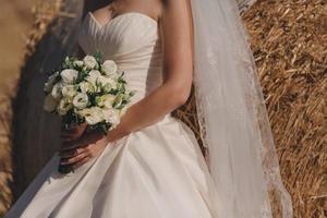 Die Braut in einem eleganten Hochzeitskleid hält einen schönen Blumenstrauß foto