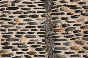 Die Oberfläche des Bürgersteigs ist wunderschön mit bunten Kieselsteinen gepflastert foto