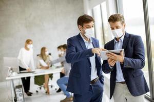 zwei maskierte Männer, die Tablette betrachten foto