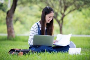 Student, der draußen auf dem Rasen studiert foto