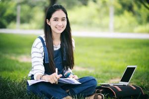 lächelnder Student, der draußen auf dem Rasen studiert foto