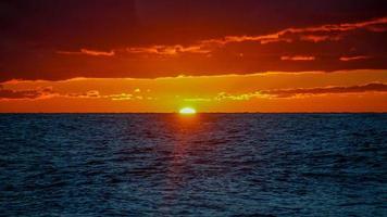 dramatischer feuriger Sonnenuntergang über der Seelandschaft foto