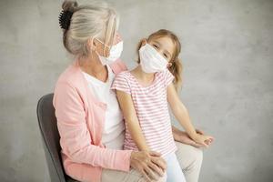 Großmutter und Enkelin tragen Masken foto