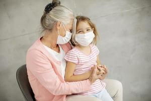 Großmutter umarmt Enkelin mit Masken foto
