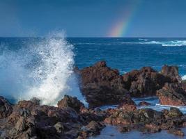 Wellen plätschern auf Felsen und ein Regenbogen auf den Kanarischen Inseln von Puerto de la Cruz Tenerife foto