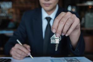 Der Bankangestellte gibt dem Kunden nach Abschluss eines Kaufvertrags ein Schlüsselhaus foto