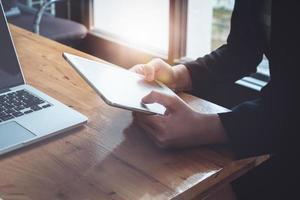 Geschäftsfrau, die Einkommenstabellen und -graphen analysiert, um Marketingkonzept unter Verwendung des Tablets und des Computers für Analyse zu planen foto