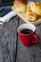 Nahaufnahme der roten Tasse des Espressokaffees mit leckeren Brötchen auf hölzernem Hintergrund foto