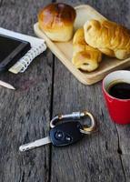 Nahaufnahme des Autoschlüssels und der roten Kaffeetasse mit Brötchen auf Holztischhintergrund foto