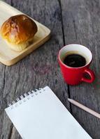 heißes Kaffeegetränk und Brötchenbrot mit Notizblock und Bleistift für Lebensstilhintergrund foto