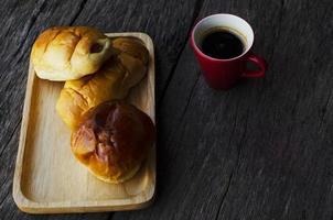 rote Tasse Espressokaffee und leckere Brötchen auf Holztischhintergrund foto