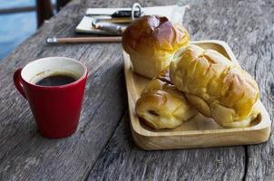 Nahaufnahme von roter Kaffeetasse und hausgemachtem Brötchenbrot auf Holztischhintergrund foto