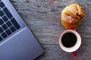 rote Kaffeetasse und leckeres Brötchen mit Laptop auf Holztisch foto