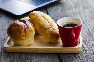 rote Kaffeetasse und leckere Brötchen auf Holzteller mit Laptop-Computer auf Holztischhintergrund foto