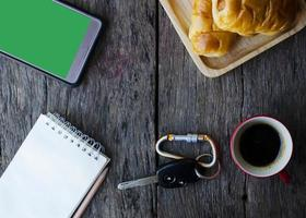 Autoschlüssel und Kaffeetasse mit leckeren Brötchen, Handy und Notizblock auf Holztischhintergrund foto