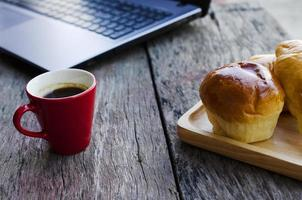 rote Kaffeetasse und leckere Brötchen mit Laptop auf Holztisch für digitale Nomade der Lifestyle-Technologie foto