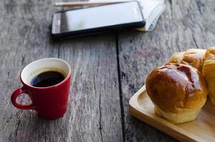 heiße Kaffee rote Tasse und Brötchen für Lifestyle-Technologie-Konzept foto