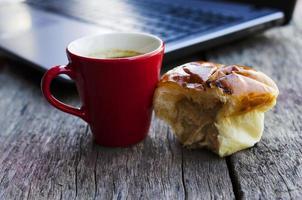 rote Kaffeetasse und Thunfischbrötchenbrot mit Laptop auf Holztisch für digitale Nomade der Lifestyle-Technologie foto