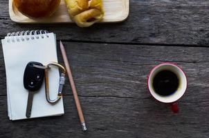 Autoschlüssel auf Notizblock mit Bleistift und roter Kaffeetasse und Brötchenbrot auf Holztischhintergrund foto
