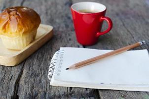 Nahaufnahme des Bleistifts mit Notizblock und Brötchen, rote Tasse auf Holztischhintergrund foto