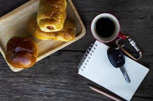 rote Kaffeetasse und Autoschlüssel und leckere Brötchen auf Holztischhintergrund foto