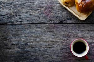 Espressokaffee und leckere Brötchen auf hölzernem Hintergrund foto