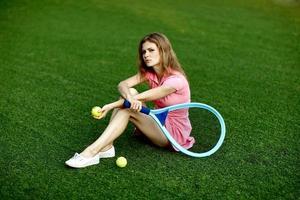 Mädchen, das auf dem Rasen eines Tennisfeldes mit einem Tennisschläger sitzt foto
