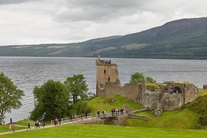 Menschen, die einen Blick auf das Urquhart Castle am Ufer des Loch Ness Schottland werfen foto