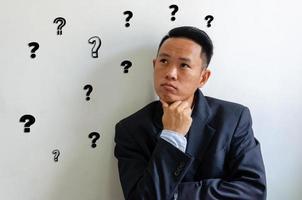 asiatischer Geschäftsmann mit einem Fragezeichen. Konzeptgeschäft. foto