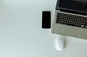 Computer Laptop und Smartphone und Maus auf Hintergrund, Draufsicht. Speicherplatz kopieren foto