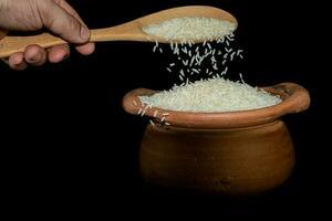 Schaufeln Sie Reis mit einer Kelle in einem Tontopf foto