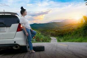 junge schöne Dame, die nahe Auto steht, um auf der öffentlichen Straße um Hilfe zu rufen foto
