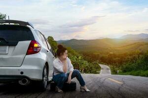 junge schöne Dame, die nahe einem Auto sitzt, um auf der öffentlichen Straße in einem Waldgebiet mit einem Berg- und Himmelhintergrund um Hilfe zu rufen foto