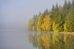 herbstlandschaft in den bergen mit bäumen, die sich im wasser am st ana see rumänien spiegeln foto