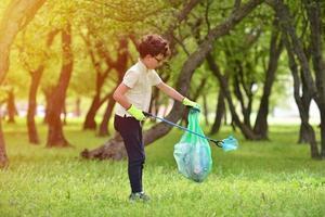 Junge nimmt Müll an einem Frühlingswald bei Sonnenuntergang auf foto