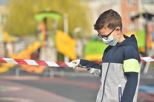 enttäuschtes einsames Kind mit Maske zum Schutz der Ausbreitung des Coronavirus foto