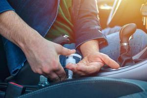 Mann im Auto desinfiziert seine Hände, um eine Coronavirus-Infektion zu vermeiden foto