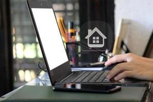 Geschäftsmann, der an Laptop für Immobilien arbeitet foto