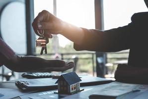 Immobilienmakler erklären sich damit einverstanden, ein Haus zu kaufen und den Kunden in den Büros ihrer Agentur Schlüssel zu geben. Konzeptvereinbarung foto