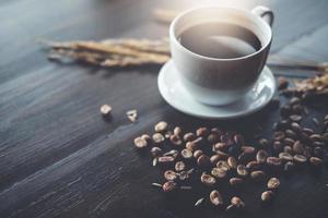 Kaffeebohne und schwarze Kaffeetasse auf Holzschreibtisch im Coffeeshop - Vintage-Effekt. foto