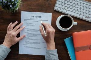 neuer Doktorand hält Lebenslauf Bewerbung mit Stift Kaffeetasse Tastatur und Notizbuch für die Bewerbung für einen Job. foto