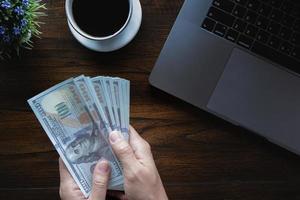 Geschäftsmann, der Dollarband mit Kaffeetasse-Computer-Laptop und Notizbuch auf Holzschreibtisch in Bürobank hält. foto
