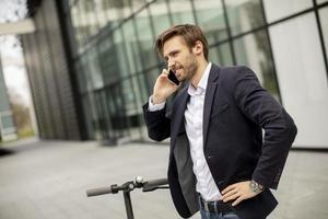 Mann, der einen geschäftlichen Anruf auf einem Roller entgegennimmt foto