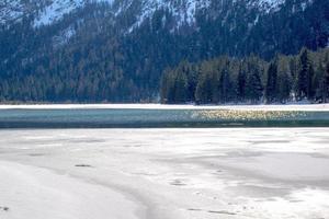Eis schmilzt auf dem Dolomitsee von Dobbiaco foto