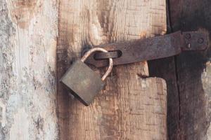 Das alte und alte Metall-Vorhängeschloss mit Rost an der Holztür ist aus Sicherheitsgründen verschlossen foto