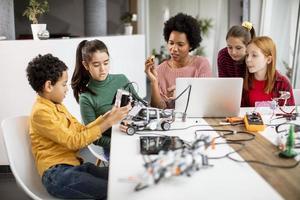 glückliche Kinder mit ihrer afroamerikanischen Wissenschaftslehrerin mit Laptop-Programmierung von elektrischem Spielzeug und Robotern im Robotik-Klassenzimmer foto