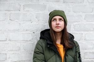 Porträt eines schönen nachdenklichen Mädchens in einem gelben Pullover und einem Khakihut foto