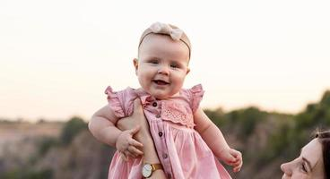 lachende Mutter hebt ihre entzückende kleine Tochter in die Luft foto