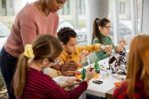 Afroamerikaner-Wissenschaftslehrerin mit Gruppe von Kindern, die elektrisches Spielzeug und Roboter am Robotik-Klassenzimmer programmieren foto